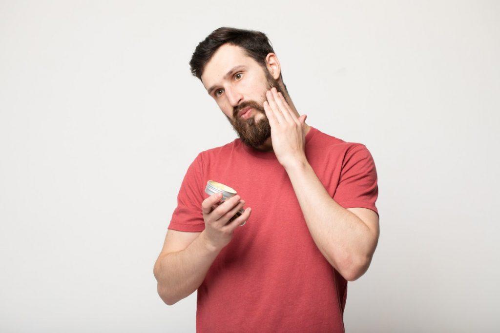 uomo applica il suo balsamo da barba
