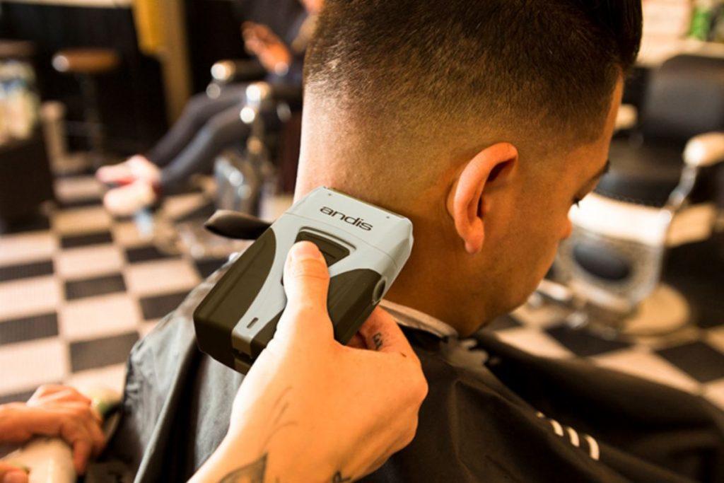 barbiere utilizza il suo rasoio Andis Profoil Lithium su un cliente