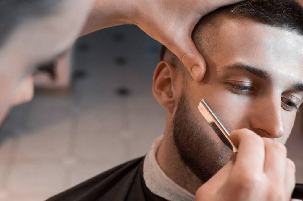barbiere insegna al proprio cliente come impugnare e utilizzare il rasoio a mano libera