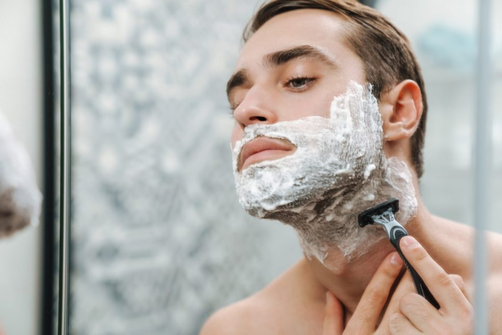 uomo si rade con il suo rasoio a mano libera con lame intercambiabili