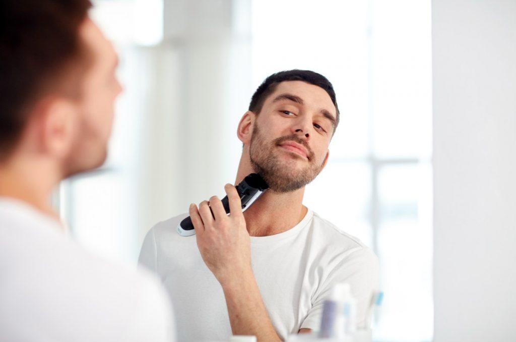 uomo si sistema la barba con un regolabarba