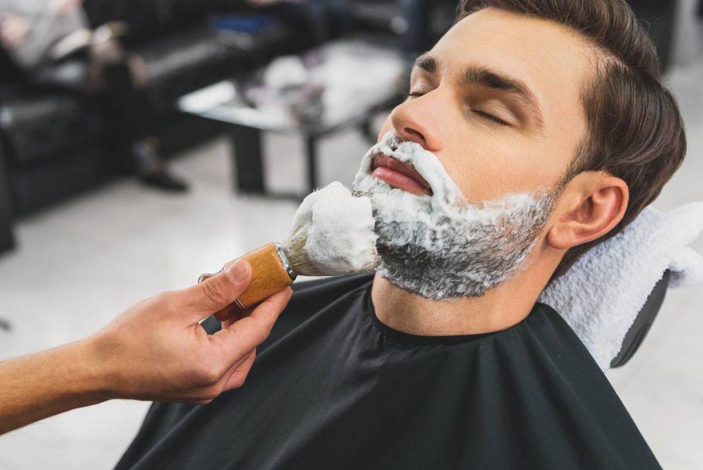 ragazzo si fa tagliare la barba e il barbiere usa un pennello in tasso