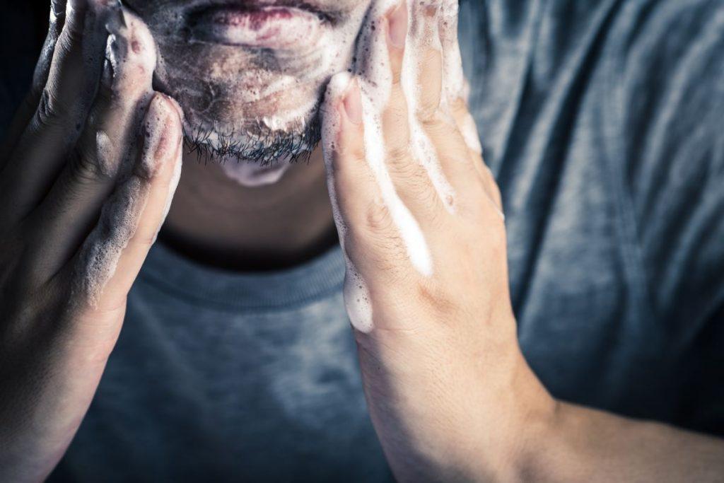 uomo lava il suo viso con un sapone da barba specifico