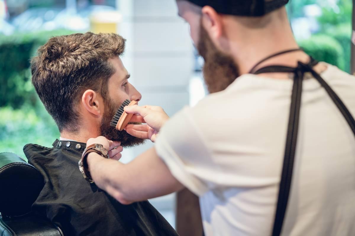 barbiere utilizza la sua spazzola da barba per pettinare la barba del cliente