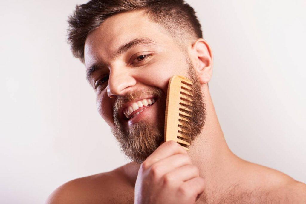 uomo si pettina la sua barba con una spazzola ad hoc