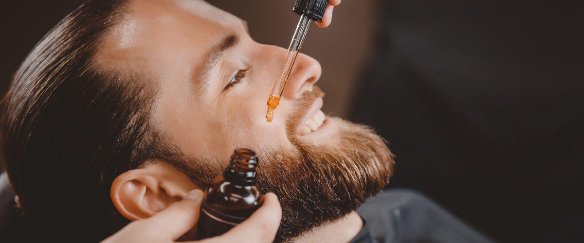 barbiere utilizza l'olio da barba sul suo cliente