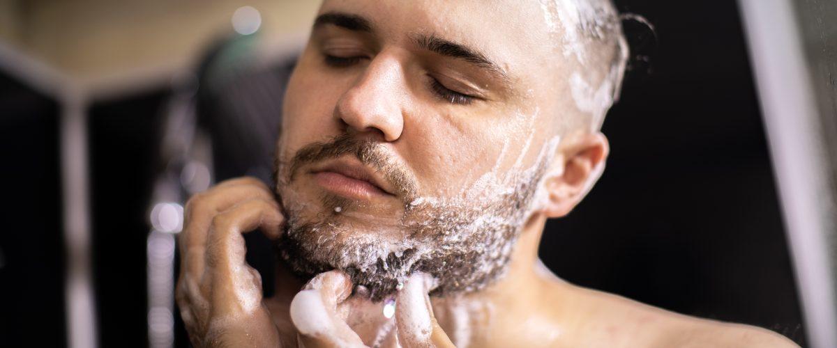 uomo lava la barba con uno shampoo apposito