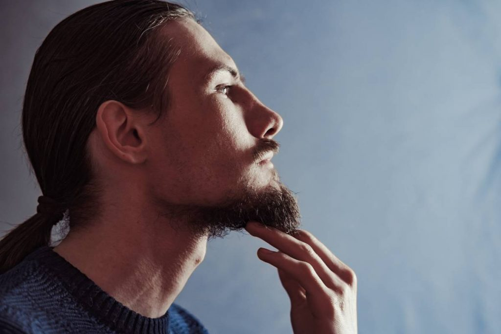 uomo tocca la sua barba con il pizzetto più lungo