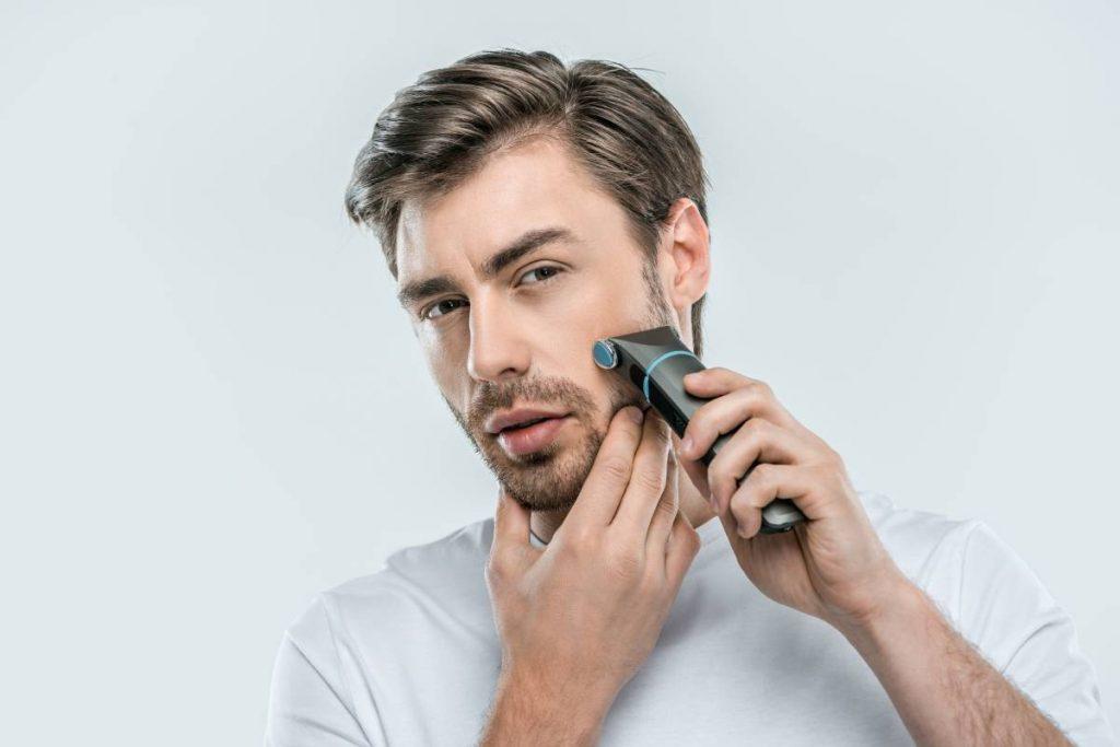uomo davanti lo specchio rade la sua barba con il miglior rasoio elettrico